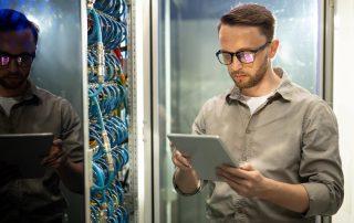 engineer using tablet in server room
