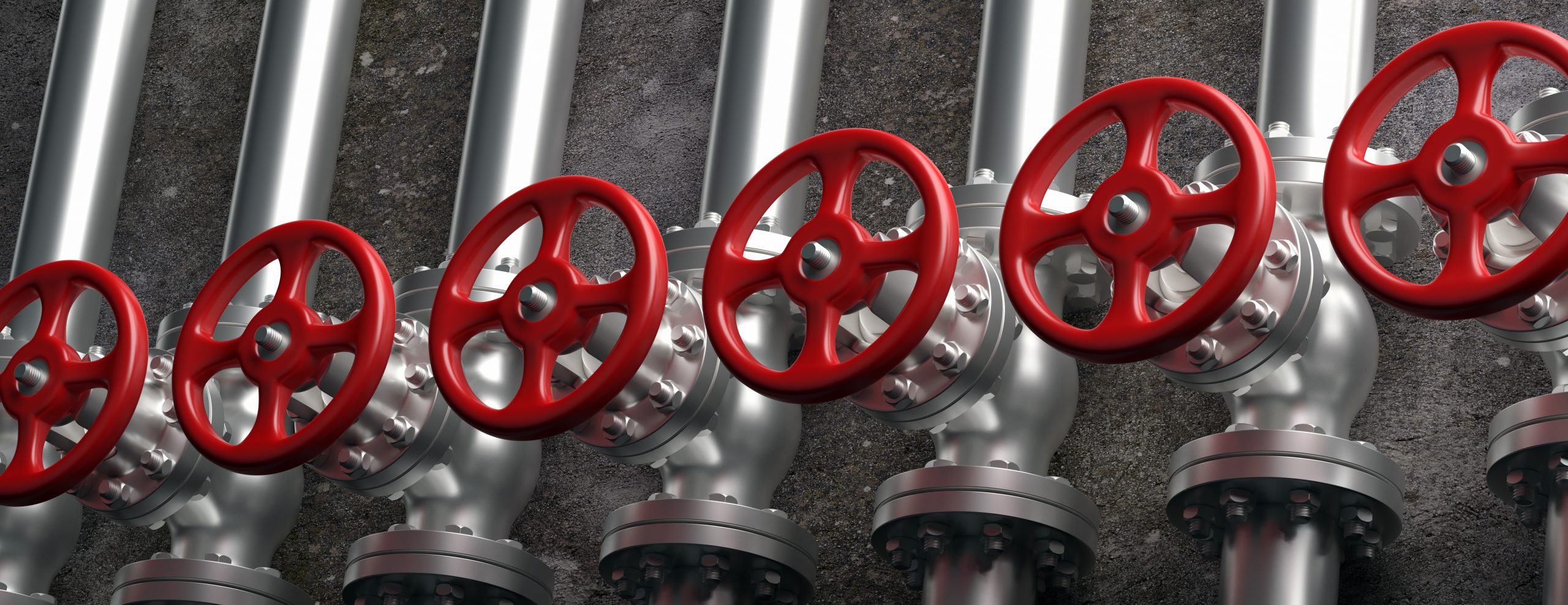 indsutrial pipelines and valves with red wheels on
