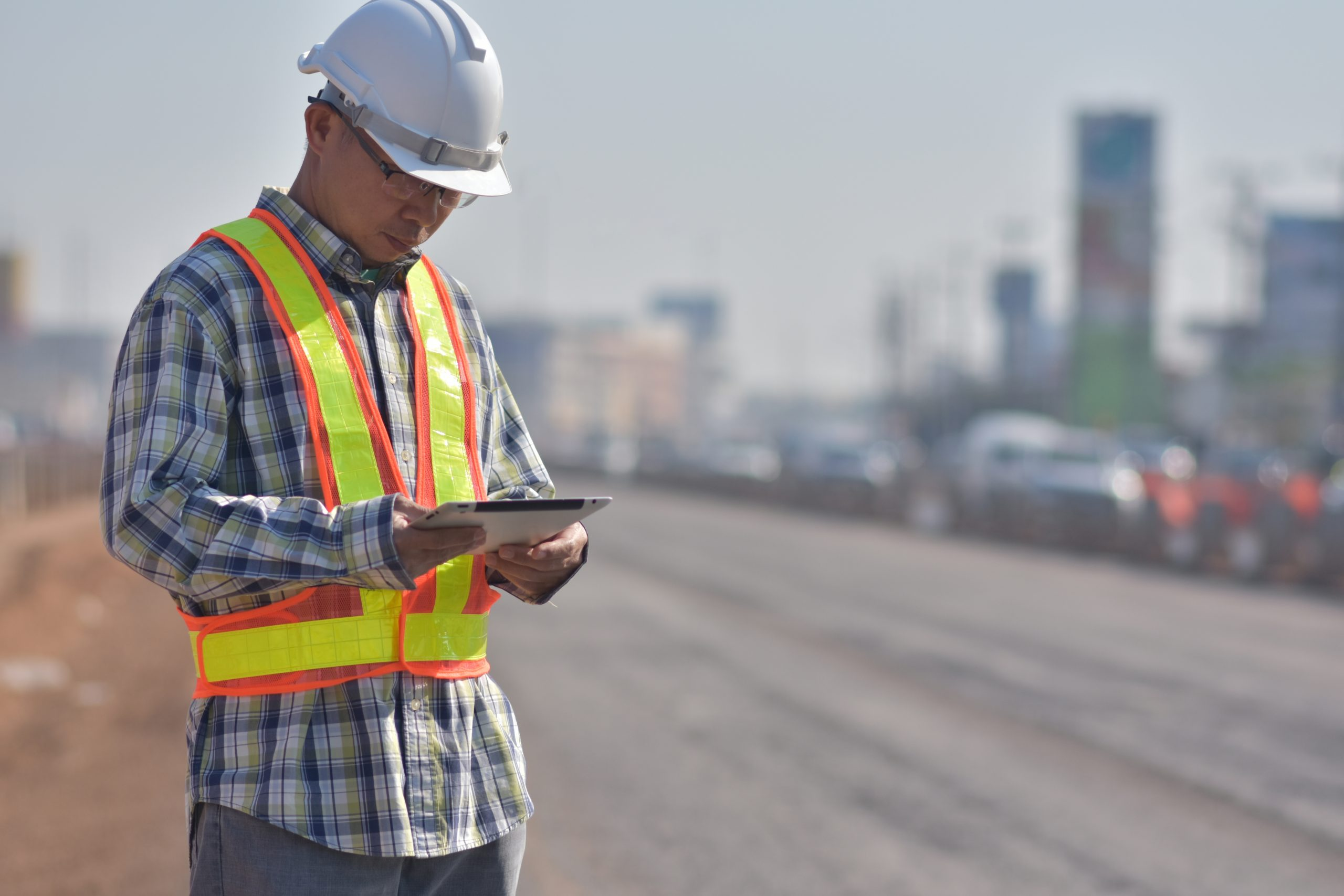 Senior Engineering holding tablet data technology working on road construction site