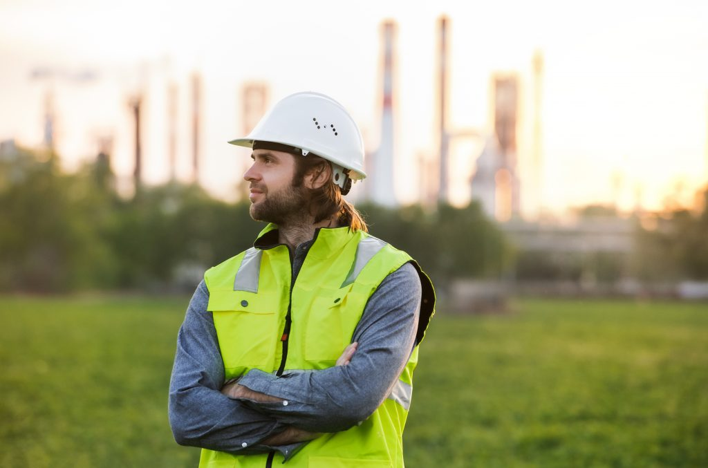 Young engineer standing outdoors by oil refinery, arms crossed.