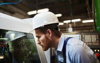 Bearded manual worker in work helmet watching for