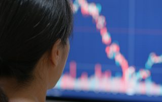 Woman watch on stock market data on computer